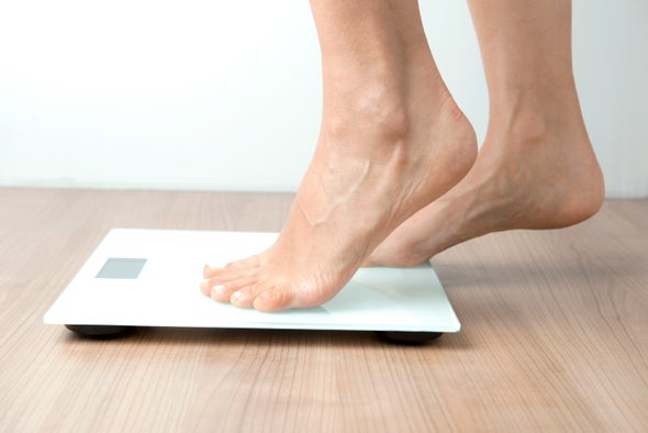 Woman's feet weighing herself on scale