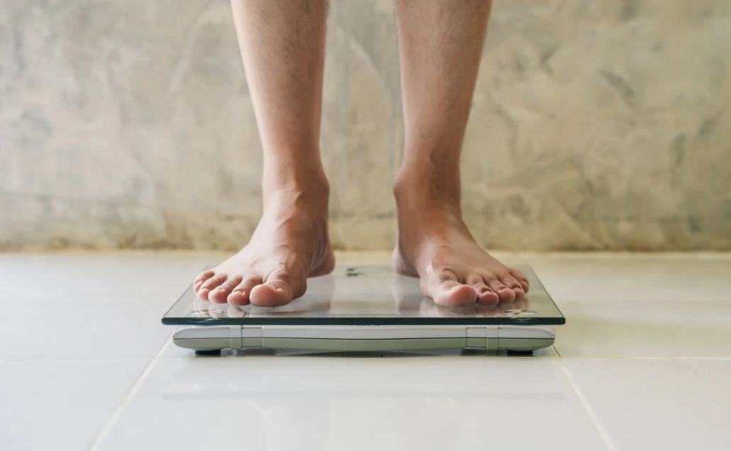 Man's feet weighing himself on scale