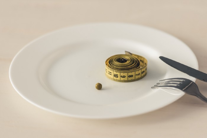 Tape measure and pea on dinner plate