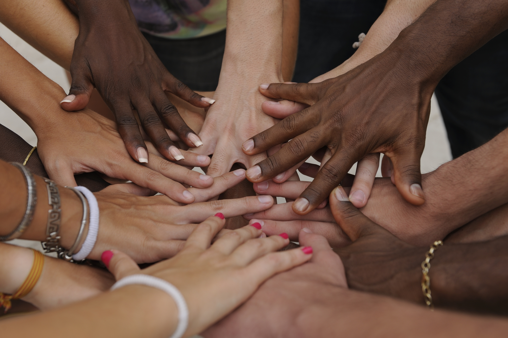 group of diverse people joining hands